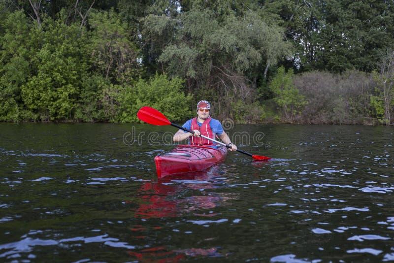 用浆划皮船的人背面图在有妇女的湖在背景中 在湖结合划皮船在一个晴天 库存图片