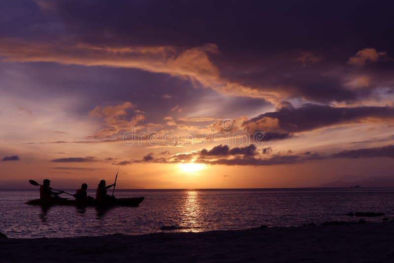 用浆划皮船的家庭由海 免版税库存照片