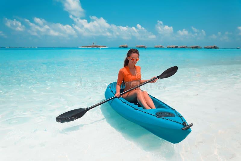 用浆划皮船的性感的浅黑肤色的男人 探索镇静热带海湾的妇女 马尔代夫 体育,休闲 夏天水上运动,冒险 免版税库存照片