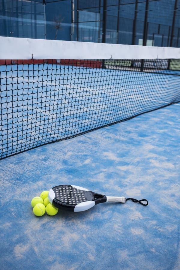 用浆划网球拍和球在法院人为草 库存照片