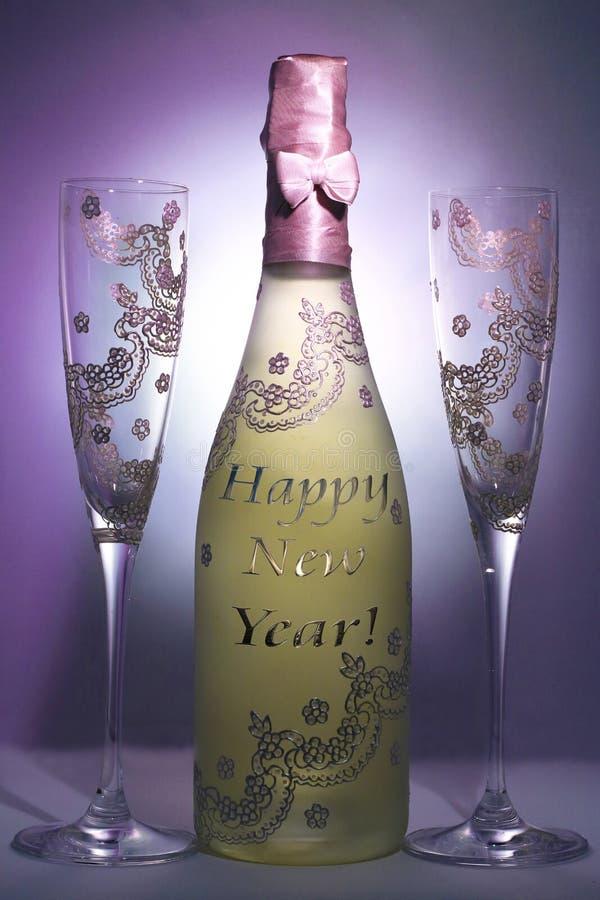 用消息新年好和两块玻璃装饰的瓶香槟 免版税库存图片