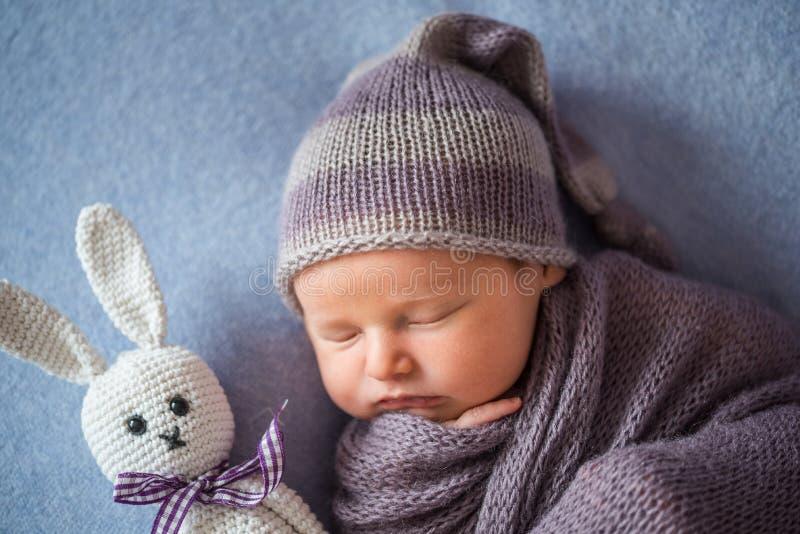 用深紫色盖的微小的睡觉的新出生的婴孩上色了套 库存图片