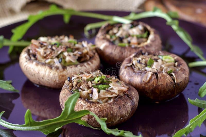 用火腿、大蒜、蘑菇、洋葱和欧芹做馅的烤棕蘑菇 图库摄影