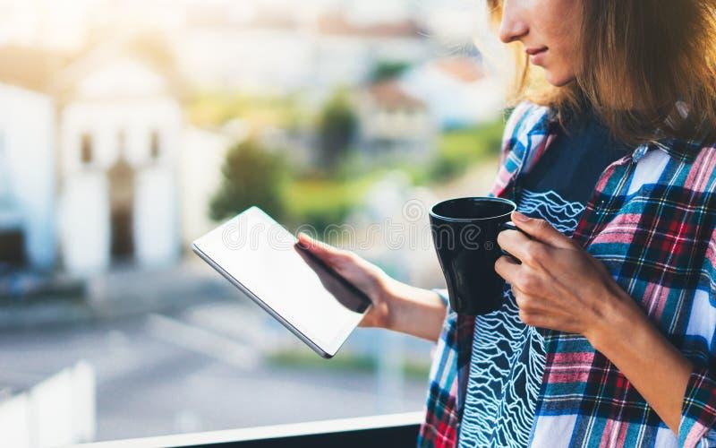 用片剂技术和饮料咖啡,女孩人在背景Sun City,女性手发短信的藏品计算机的行家女孩 免版税图库摄影