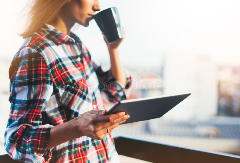 用片剂技术和饮料咖啡,女孩人的行家女孩拿着在背景Sun City,发短信给m的女性手的计算机 免版税库存照片