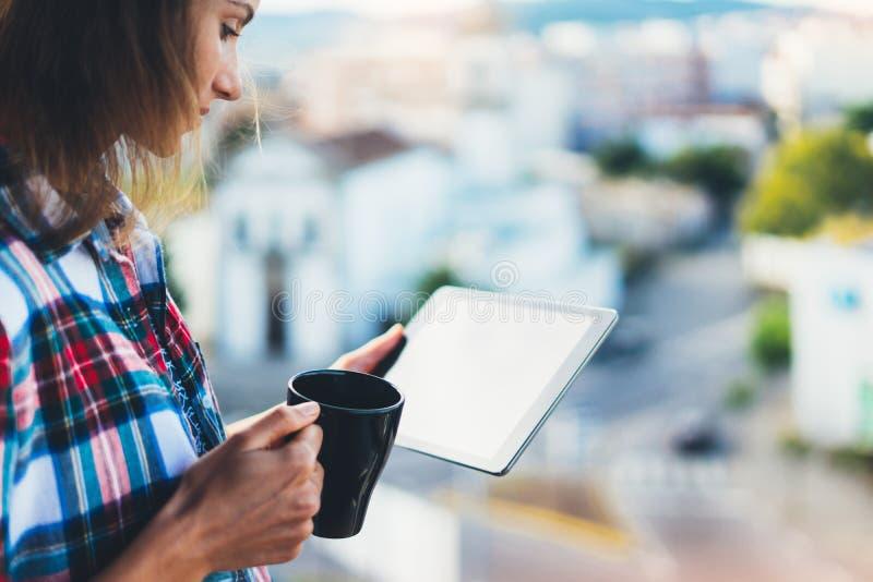 用片剂技术和饮料咖啡,女孩人的行家女孩拿着在背景Sun City,发短信给m的女性手的计算机 免版税库存图片