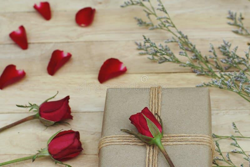 用玫瑰和其他花装饰的Eco友好的棕色包装纸礼物盒礼物在木背景,华伦泰装饰物 免版税库存照片