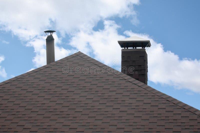 用现代平的沥青防水涂层盖的屋顶在蓝天下 免版税库存照片