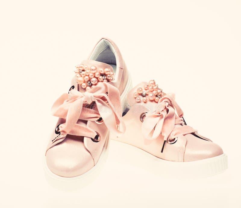 用珍珠和妇女的鞋类装饰的女孩成串珠状 对有天鹅绒丝带的淡粉红的女性运动鞋 时髦 库存图片