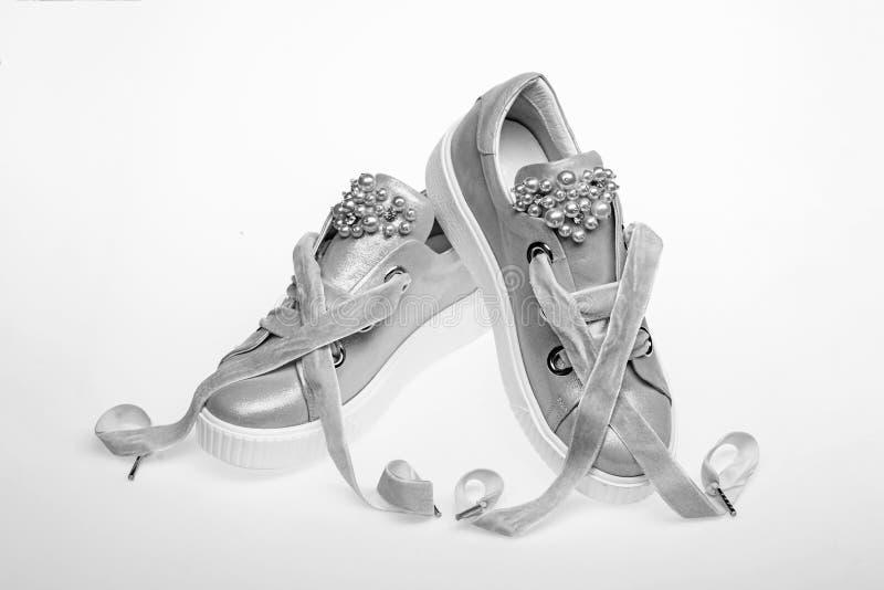 用珍珠和妇女的鞋类装饰的女孩成串珠状 对有天鹅绒丝带的淡粉红的女性运动鞋 免版税库存图片
