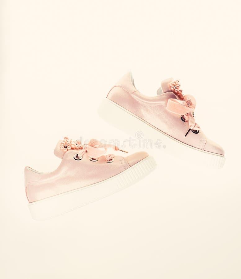 用珍珠和妇女的鞋类装饰的女孩成串珠状 时髦运动鞋概念 在白色隔绝的逗人喜爱的鞋子 库存图片
