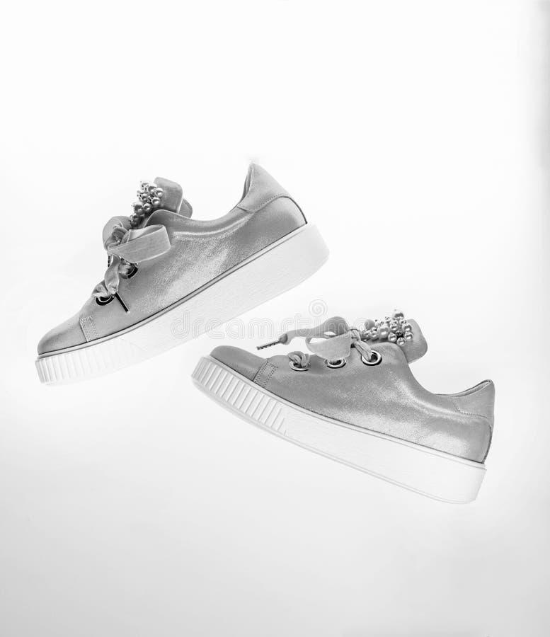 用珍珠和妇女的鞋类装饰的女孩成串珠状 时髦运动鞋概念 在白色隔绝的逗人喜爱的鞋子 库存照片