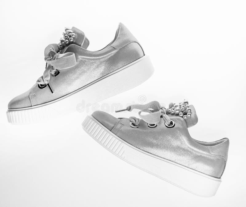 用珍珠和妇女的鞋类装饰的女孩成串珠状 时髦运动鞋概念 对淡粉红的女性运动鞋与 免版税库存照片