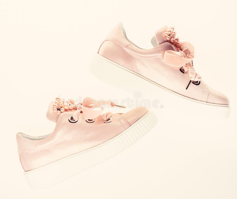 用珍珠和妇女的鞋类装饰的女孩成串珠状 时髦运动鞋概念 对淡粉红的女性运动鞋与 免版税库存图片