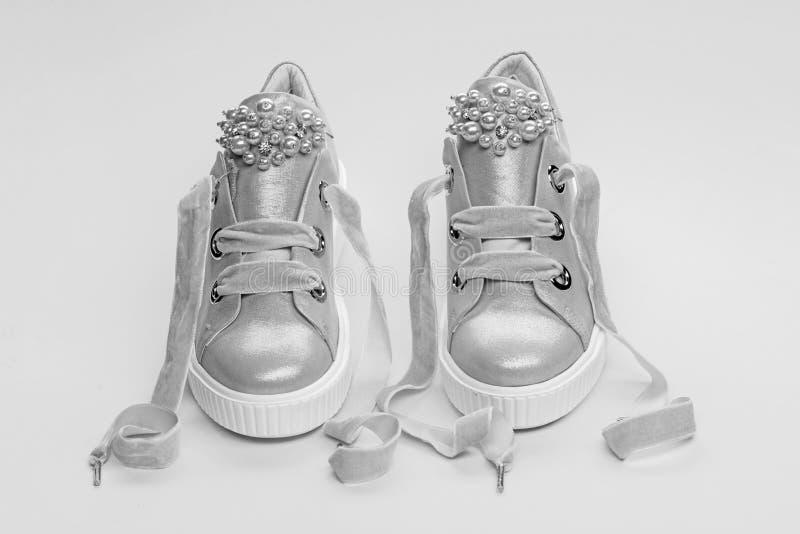 用珍珠或妇女的鞋类装饰的女孩成串珠状 在黄色背景的逗人喜爱的鞋子 舒适的鞋类概念 库存图片