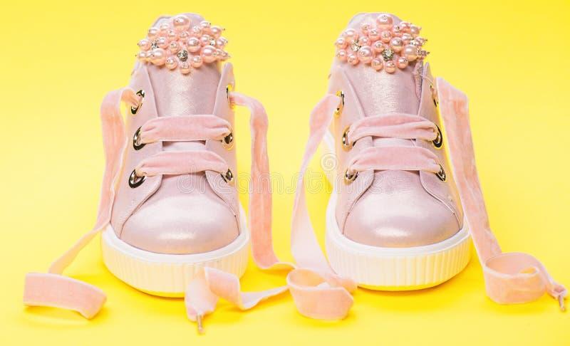 用珍珠或妇女的鞋类装饰的女孩成串珠状 对有天鹅绒丝带的淡粉红的女性运动鞋 孩子的 图库摄影