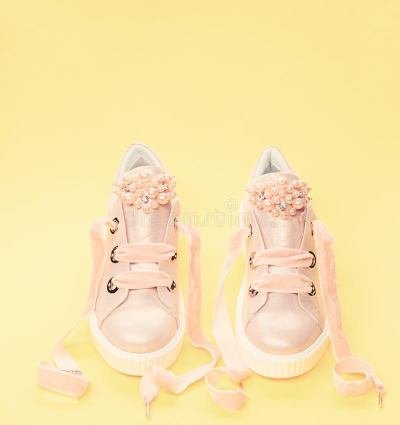 用珍珠或妇女的鞋类装饰的女孩成串珠状 对有天鹅绒丝带的淡粉红的女性运动鞋 逗人喜爱 图库摄影