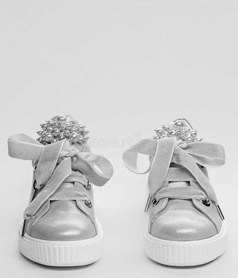 用珍珠或妇女的鞋类装饰的女孩成串珠状 舒适的鞋类概念 对淡粉红的女性运动鞋 免版税库存图片