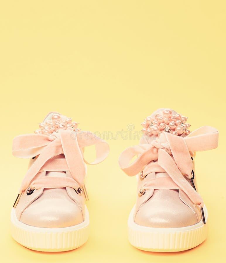 用珍珠或妇女的鞋类装饰的女孩成串珠状 舒适的鞋类概念 对淡粉红的女性运动鞋 免版税库存照片