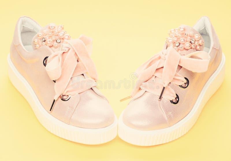 用珍珠或妇女的鞋类装饰的女孩成串珠状 迷人的鞋类概念 对淡粉红的女性运动鞋 库存照片