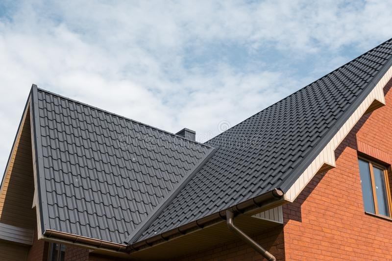 用瓦片作用PVC盖的现代屋顶涂上了棕色金属屋顶板料 免版税库存照片