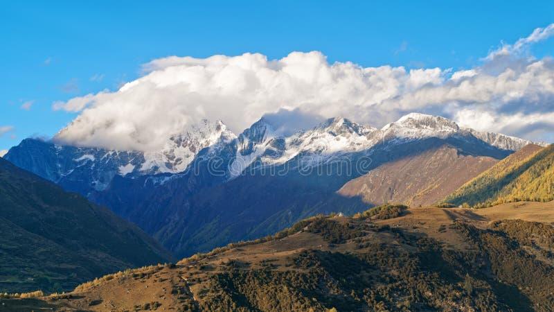 用白色云彩盖的美丽的雪山 中国四川的风景'四个女孩山'雪山山脉在秋天 免版税图库摄影