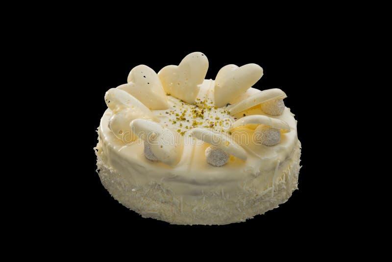 用白色心脏装饰的白色巧克力蛋糕 库存照片