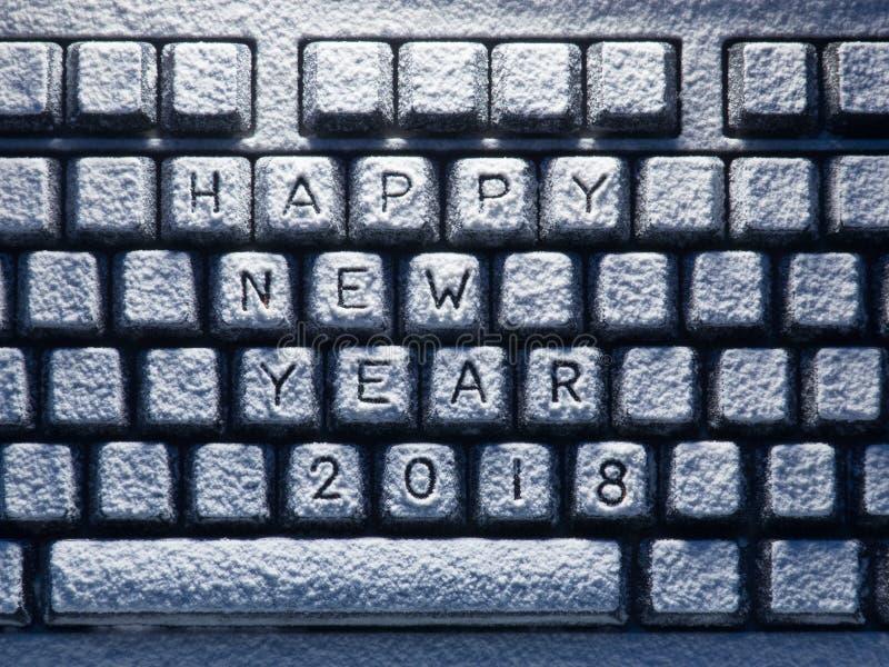 用白色雪盖的桌面键盘与标题新年好2018年 免版税库存照片