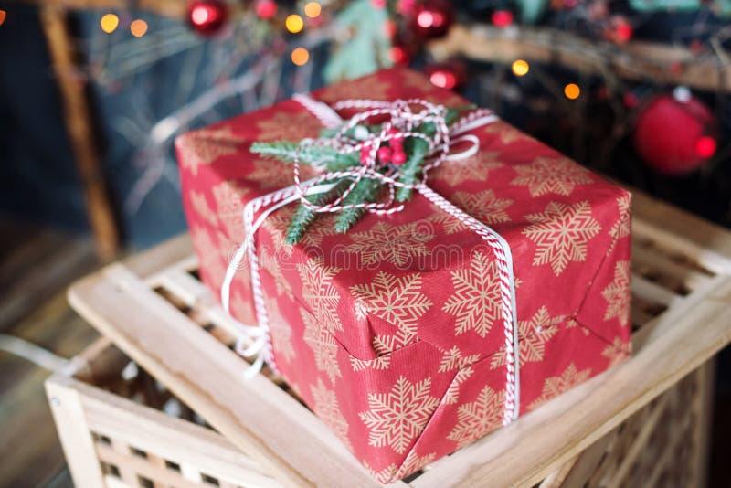 用白色雪花和一个云杉的分支装饰的红色圣诞礼物箱子 免版税图库摄影