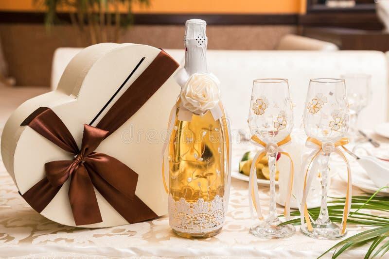 用的鞋带和杯在婚姻的桌上的香槟装饰的一个瓶新娘和新郎 库存图片