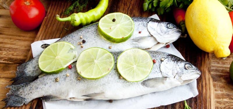 用石灰切片和干胡椒晒干的未加工的鳟鱼 免版税图库摄影