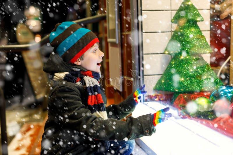 用礼物在时尚冬天给做窗口购物穿衣装饰的滑稽的愉快的孩子, xmas树 免版税库存图片