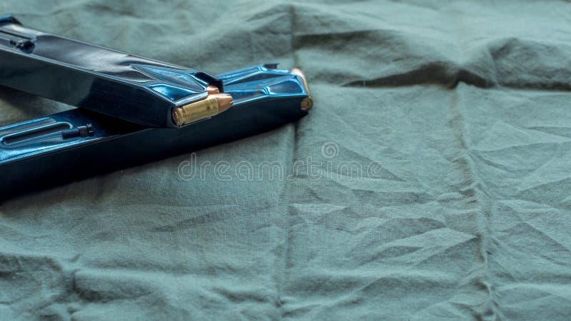 用空心点弹药装载的黑钢手枪手枪杂志,休息在草绿色布料背景 免版税库存图片