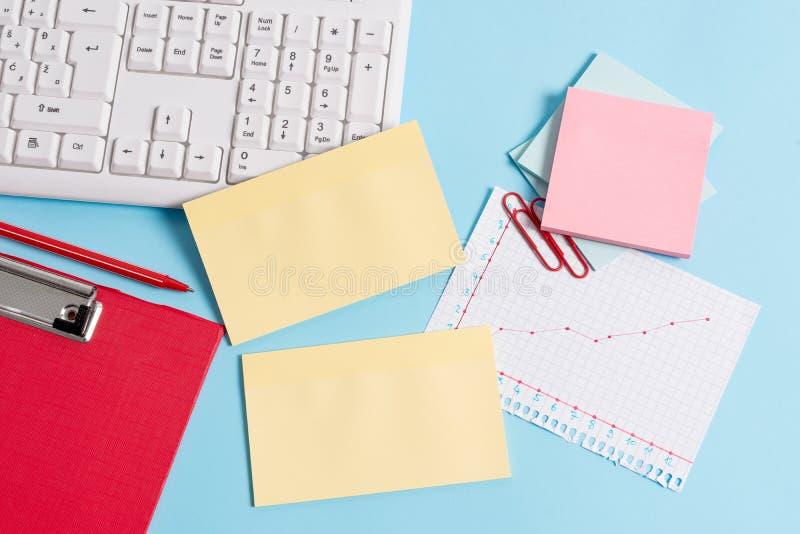 用空的纸笔记、键盘和办公用具的不同的大小的浅兰的书桌 ?? 库存图片