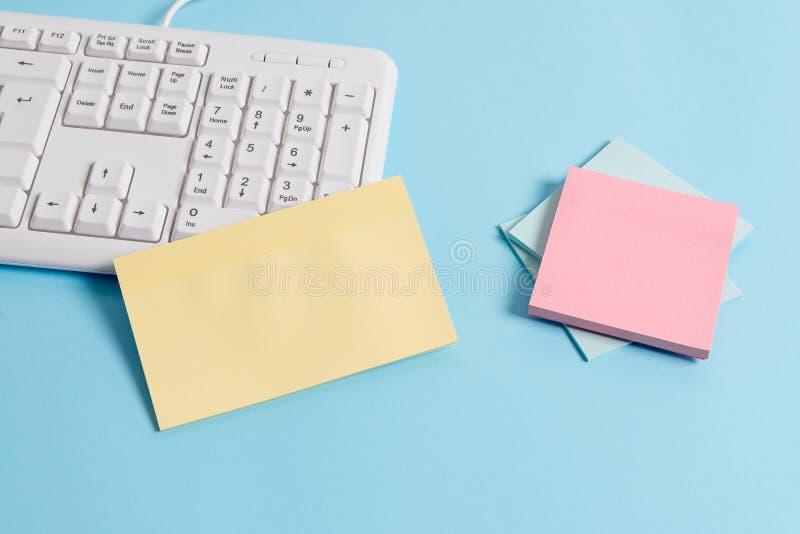 用空的纸笔记、键盘和办公用具的不同的大小的浅兰的书桌 ?? 免版税库存照片