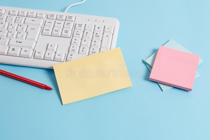 用空的纸笔记、键盘和办公用具的不同的大小的浅兰的书桌 ?? 免版税库存图片