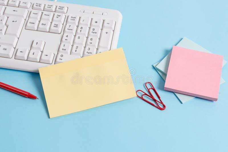 用空的纸笔记、键盘和办公用具的不同的大小的浅兰的书桌 ?? 库存照片