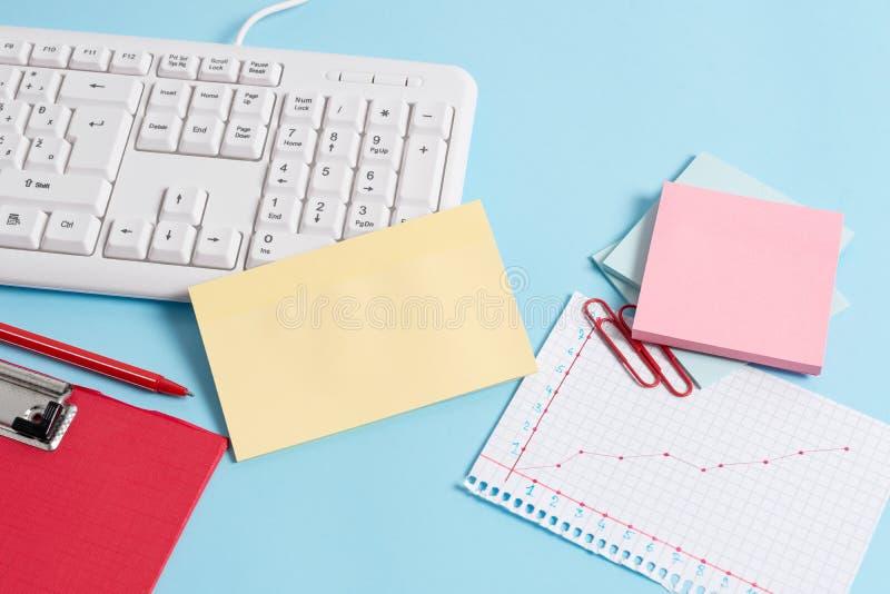 用空的纸笔记、键盘和办公用具的不同的大小的浅兰的书桌 ?? 免版税图库摄影