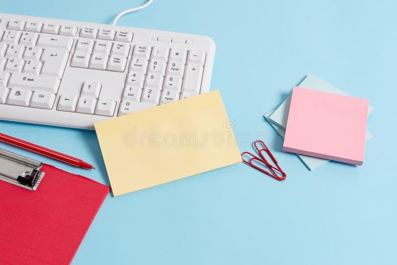 用空的纸笔记、键盘和办公用具的不同的大小的浅兰的书桌 ?? 图库摄影