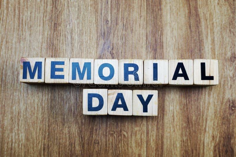 用立方体在木背景的字母表信件创造的阵亡将士纪念日词 库存照片