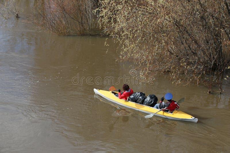 用筏子运送河 游人在洪水的森林河游泳在独木舟 划皮船在水位高在春天森林 库存照片