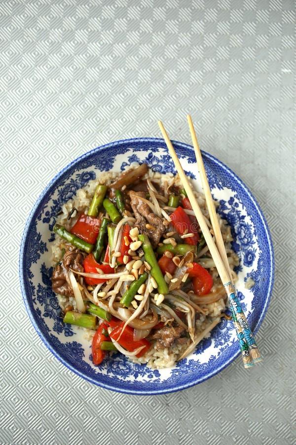 用筷子在蓝碗里泡菜 免版税图库摄影