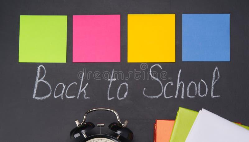 用粉笔写在黑板,回到学校、一套记录的多彩多姿的贴纸在他们和一个黑警钟 免版税库存照片