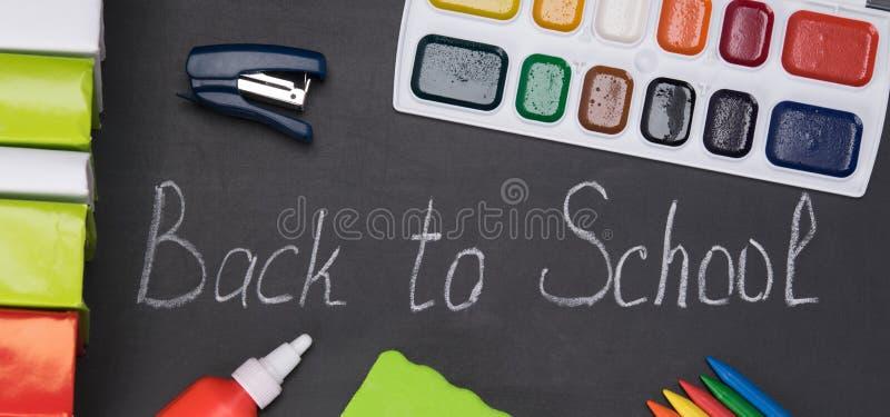 用粉笔写在whiteboard,回到学校,与套的背景研究的主题,计划在黑色 免版税图库摄影