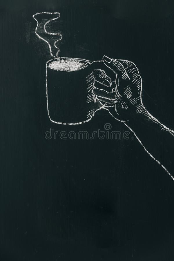 用粉笔写画手的手拿着有蒸汽的咖啡杯在黑人委员会在框架的上面附近 图库摄影