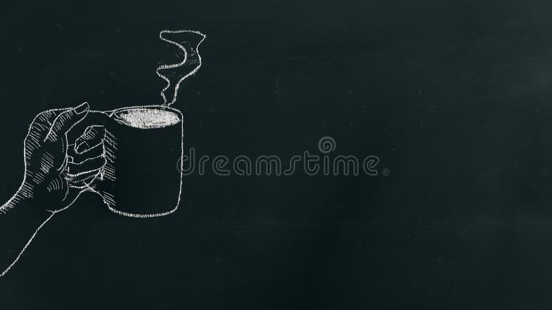 用粉笔写画手的手拿着有蒸汽的咖啡杯在黑人委员会在框架的左边 库存图片
