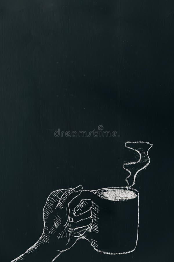 用粉笔写画手的手拿着有近蒸汽的咖啡杯在黑板下面框架 库存图片
