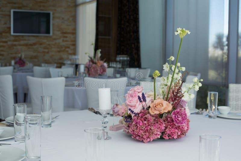 用精美鲜花服务和装饰的事件白色餐馆桌 库存照片
