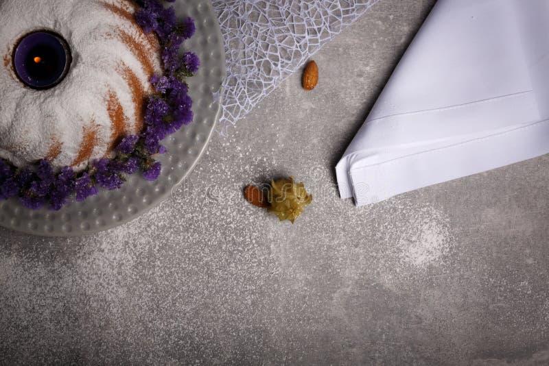 用糖粉末盖的一个鲜美圆环蛋糕的顶视图,杏仁,空泡,在灰色背景的一块白色餐巾 库存照片