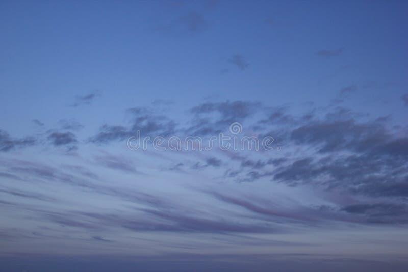 用紫罗兰色云彩条纹盖的深蓝天空  免版税库存照片